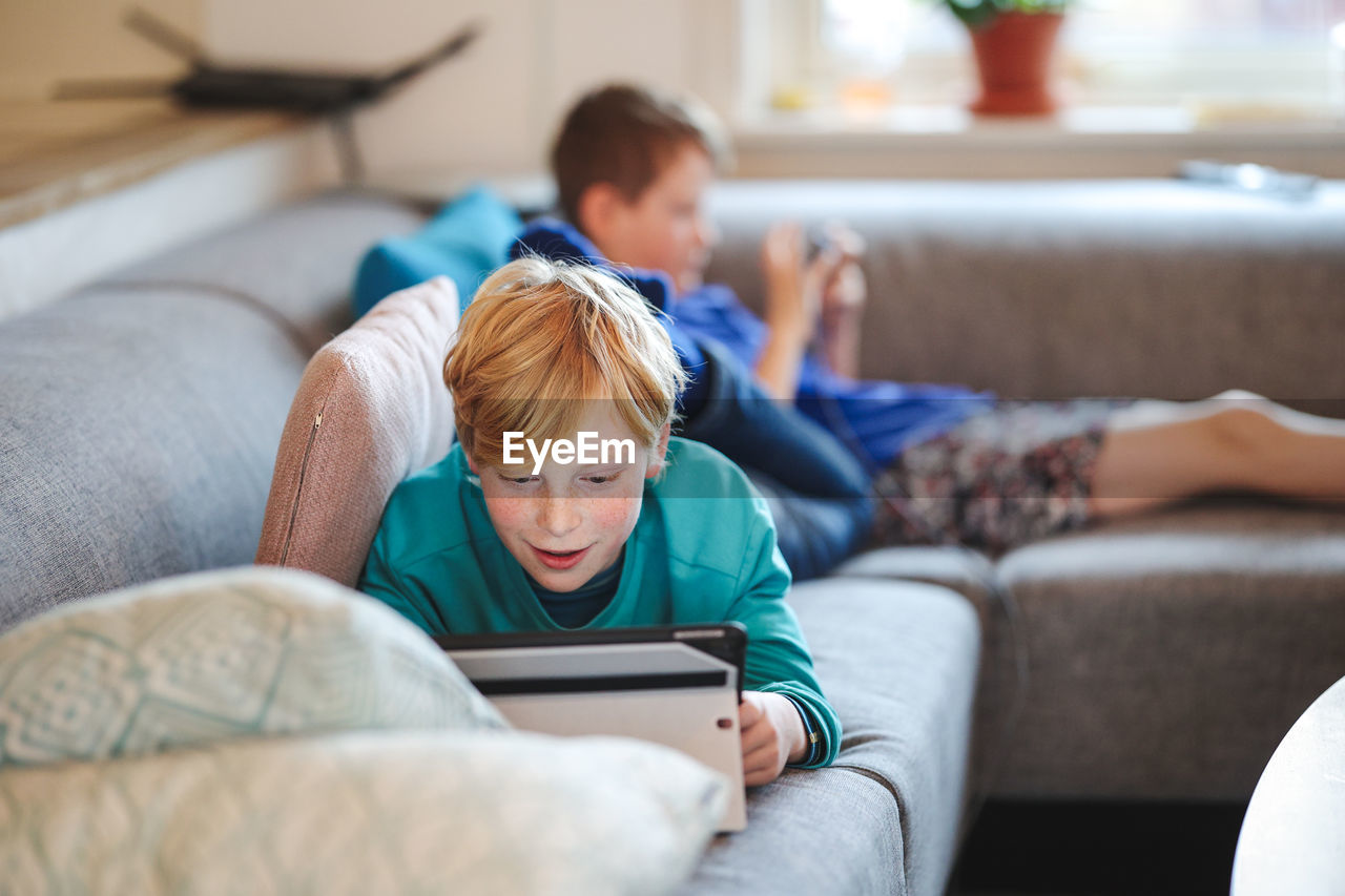 Boys on couch with tablet and phone