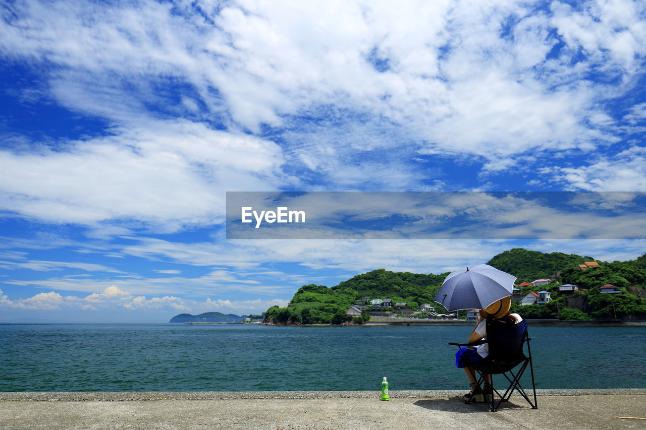 Rear View Of Woman With Umbrella Sitting At Beach Against Cloudy Sky
