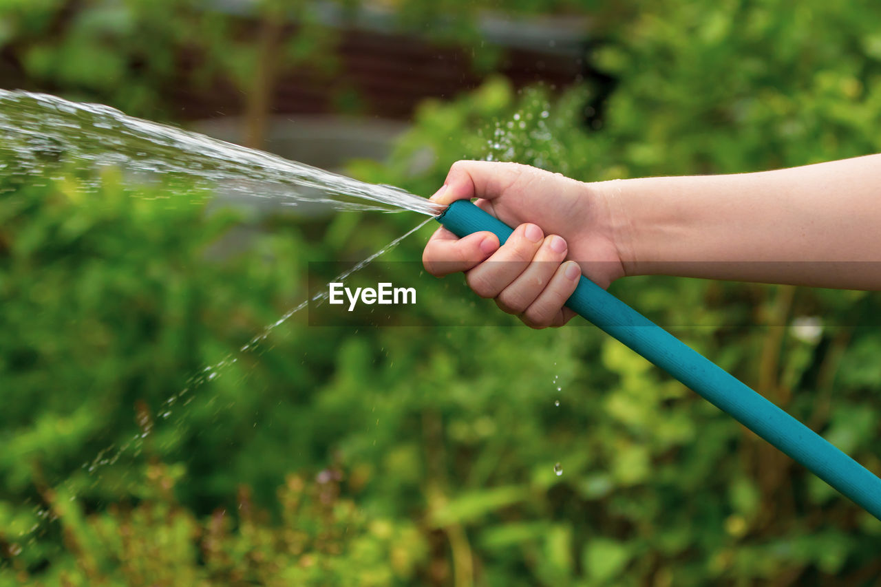 Person Spraying Water From Garden Hose At Back Yard