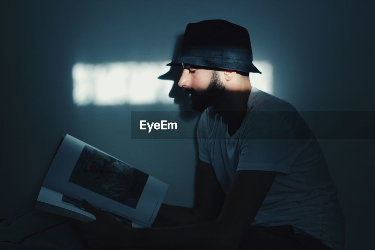 technology, wireless technology, hat, laptop, computer, communication, cap, using laptop, one person, casual clothing, internet, indoors, sitting, real people, touch screen, illuminated, young adult, night, men, liquid-crystal display, keyboard, adult, people