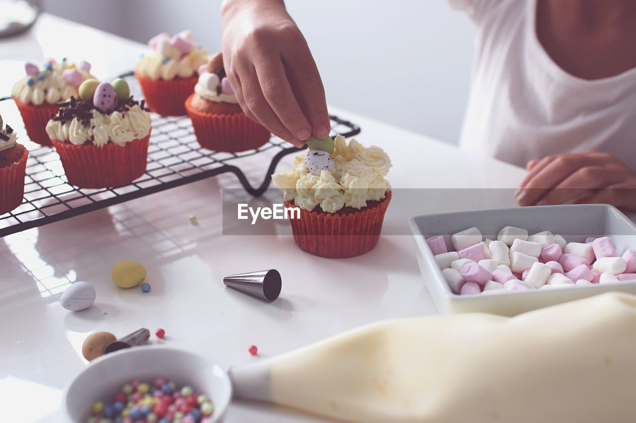 Midsection of person garnishing cupcakes on table at home