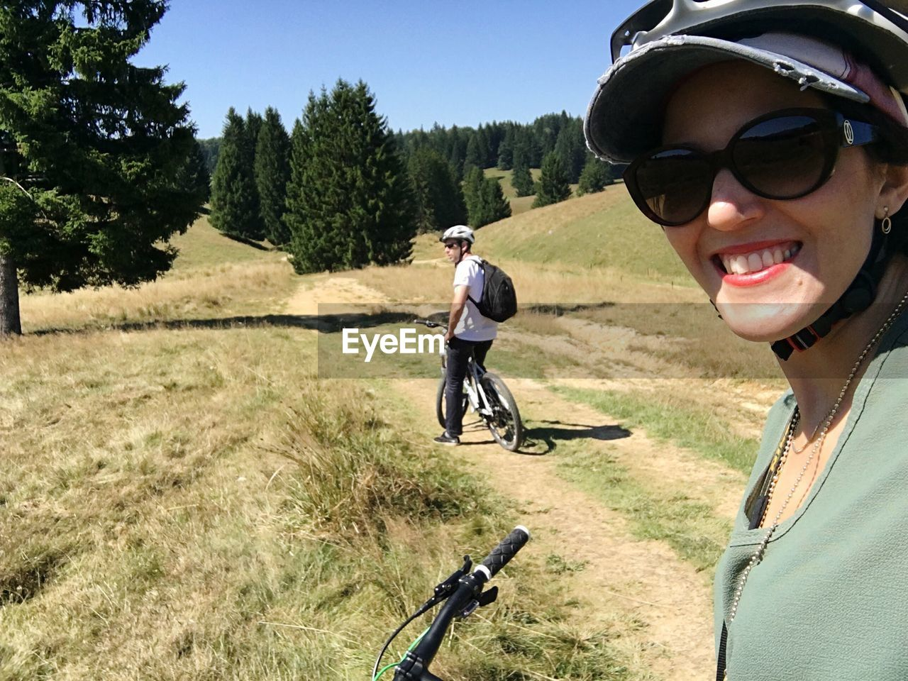 Happy woman with bicycle on field during sunny day with friend in background