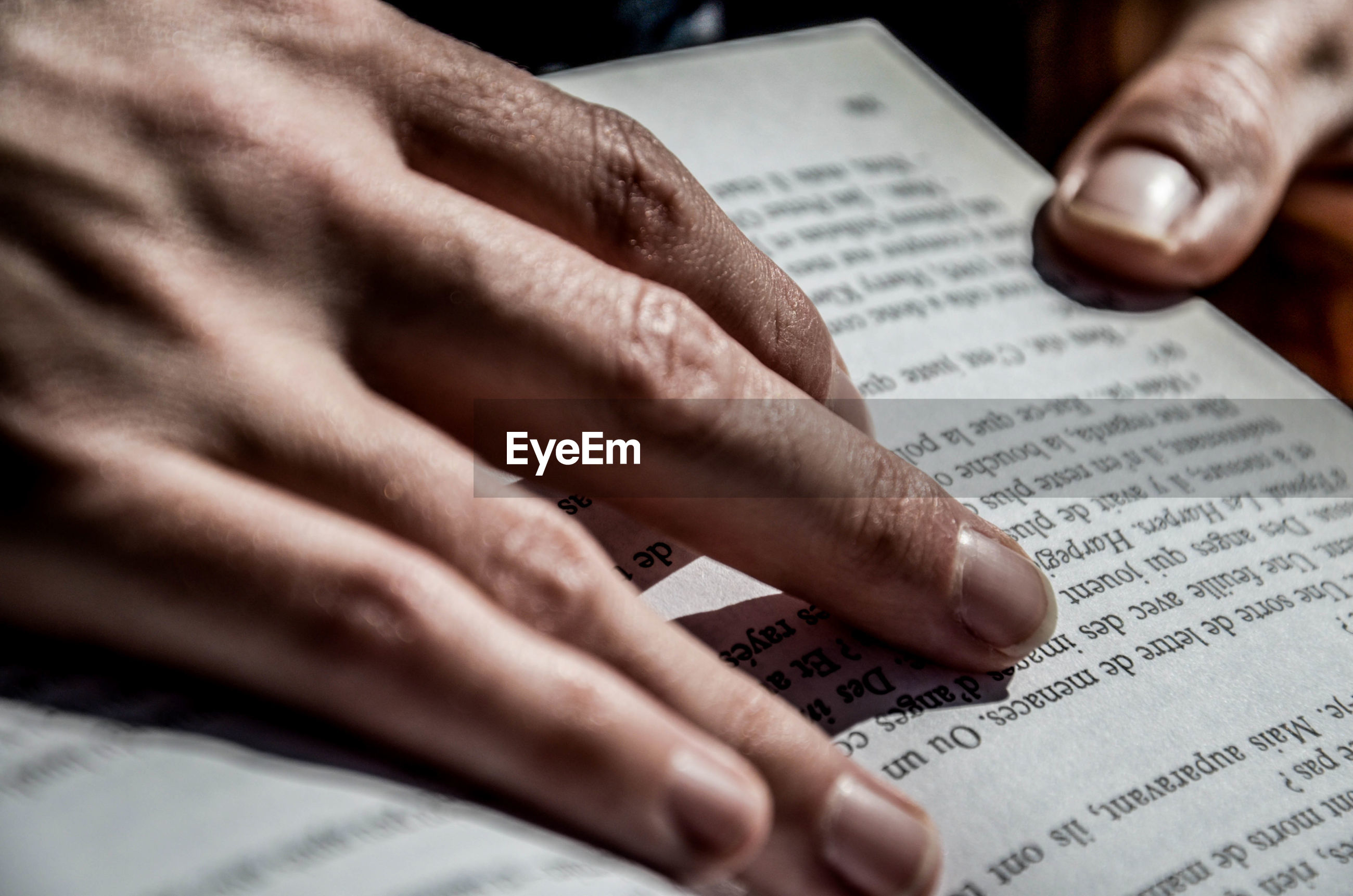 Cropped image of hands holding book