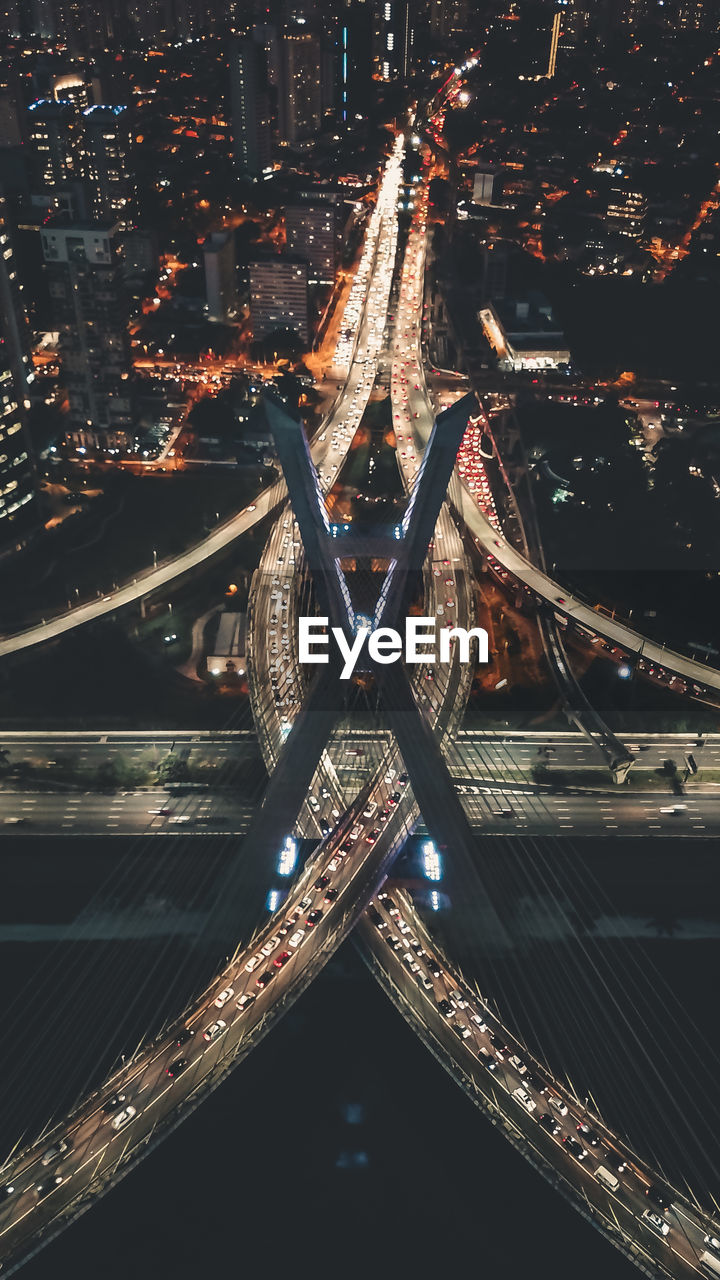 Aerial view of illuminated bridges in city at night