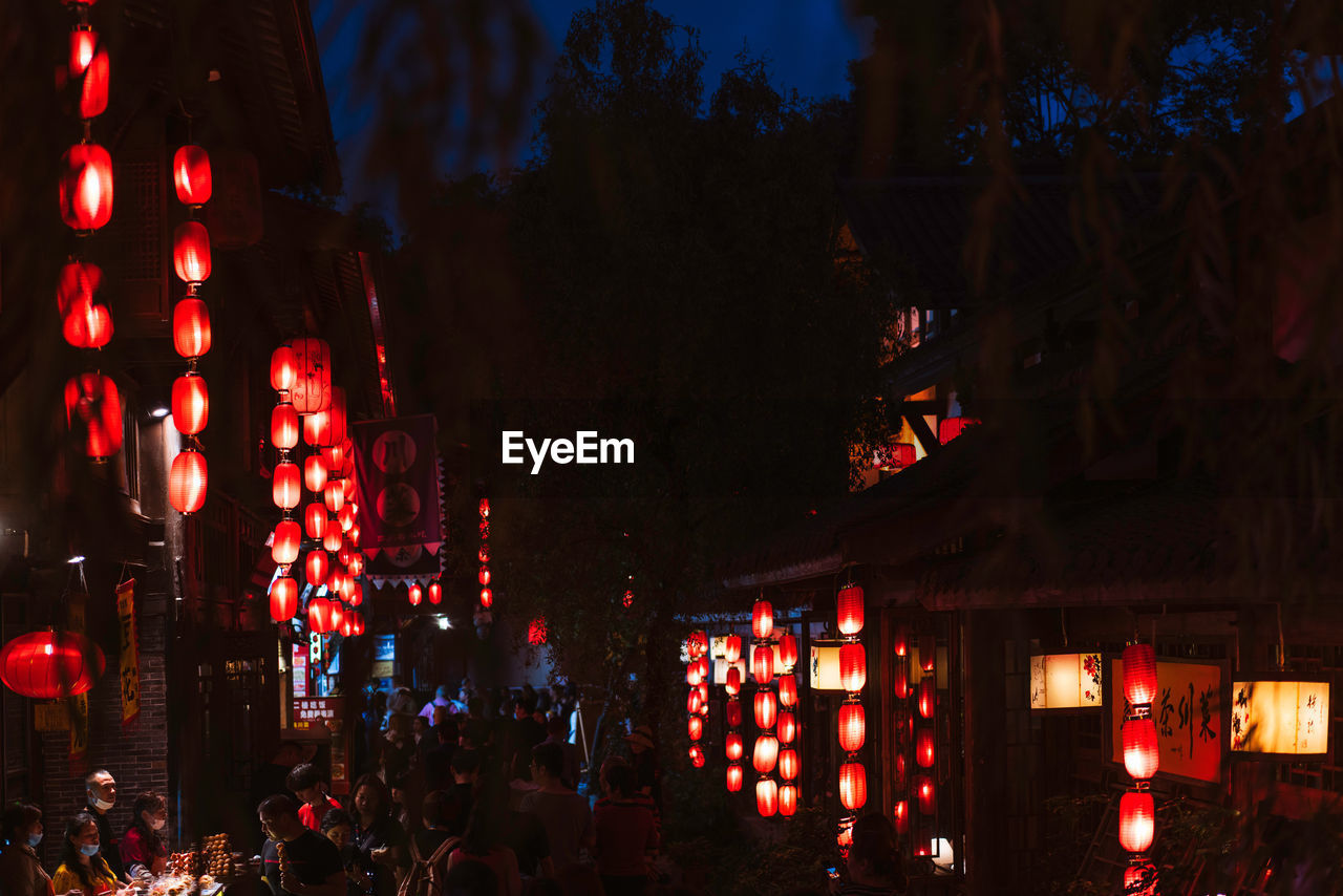 illuminated, night, lighting equipment, built structure, building exterior, architecture, city, large group of people, lantern, decoration, crowd, group of people, incidental people, women, lifestyles, real people, tree, glowing, outdoors, chinese lantern, light
