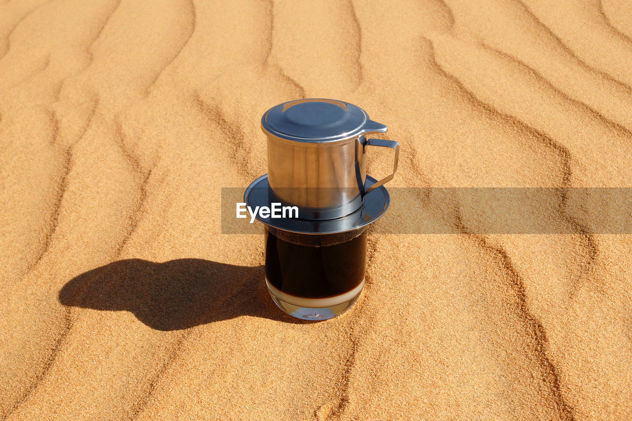sand, land, sunlight, cup, drink, still life, nature, food and drink, shadow, no people, container, high angle view, beach, coffee, mug, brown, day, indoors, coffee cup, refreshment, arid climate