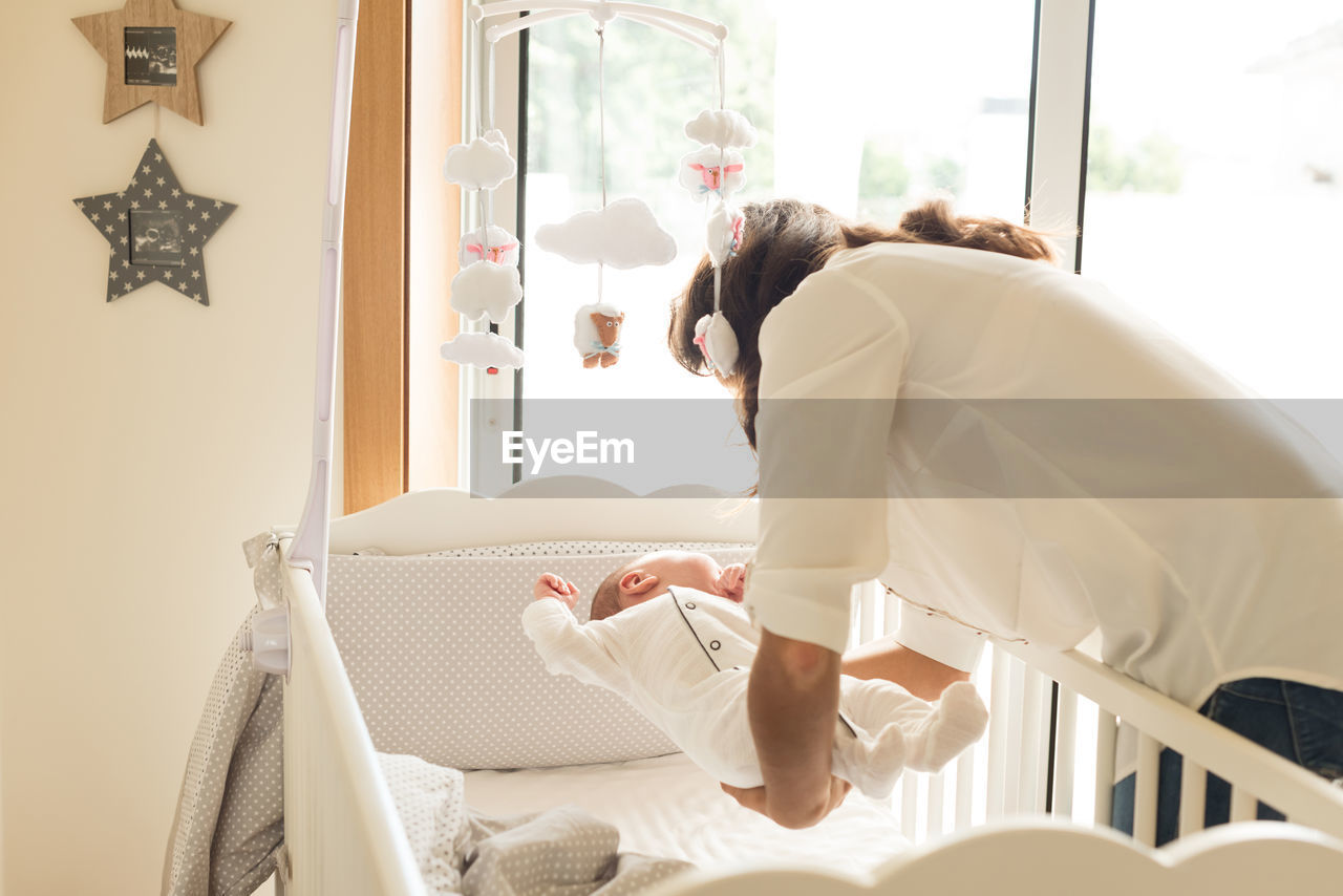 Mother Picking Up Toddler Son In Crib At Home