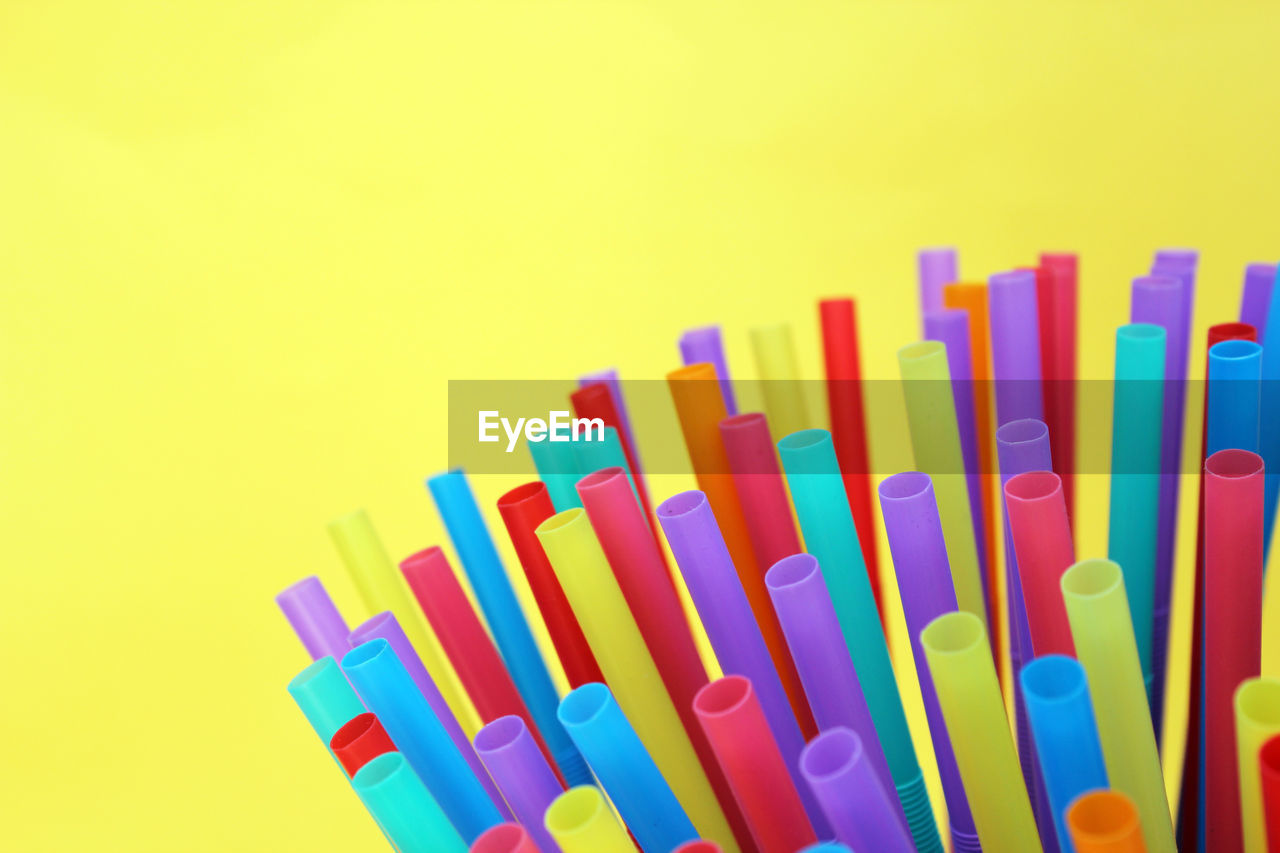 CLOSE-UP OF MULTI COLORED PENCILS OVER YELLOW BACKGROUND