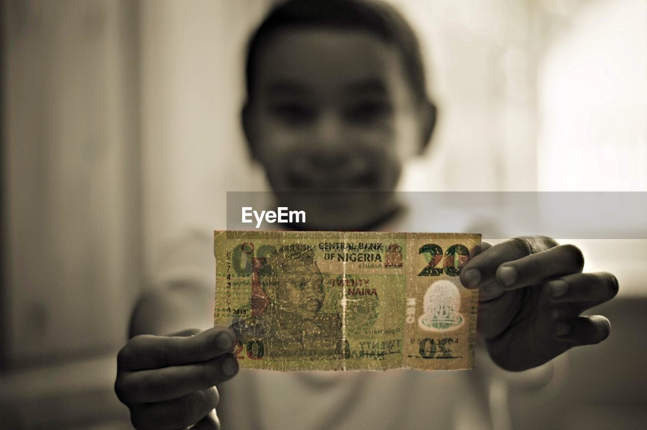 Close-up of a girl holding Nigerian note