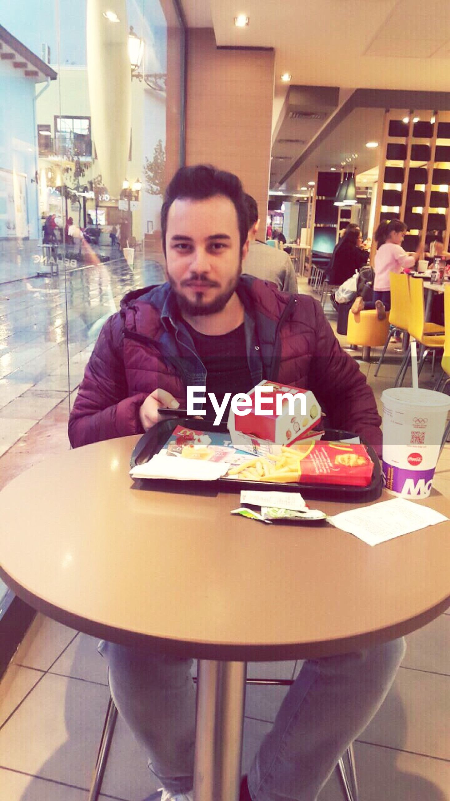looking at camera, portrait, smiling, one person, food, front view, unhealthy eating, happiness, restaurant, table, snack, people, serving food and drinks, cheerful, city, real people, standing, fast food, adults only, indoors, adult, young adult, one man only, only men, ice cream parlor, day