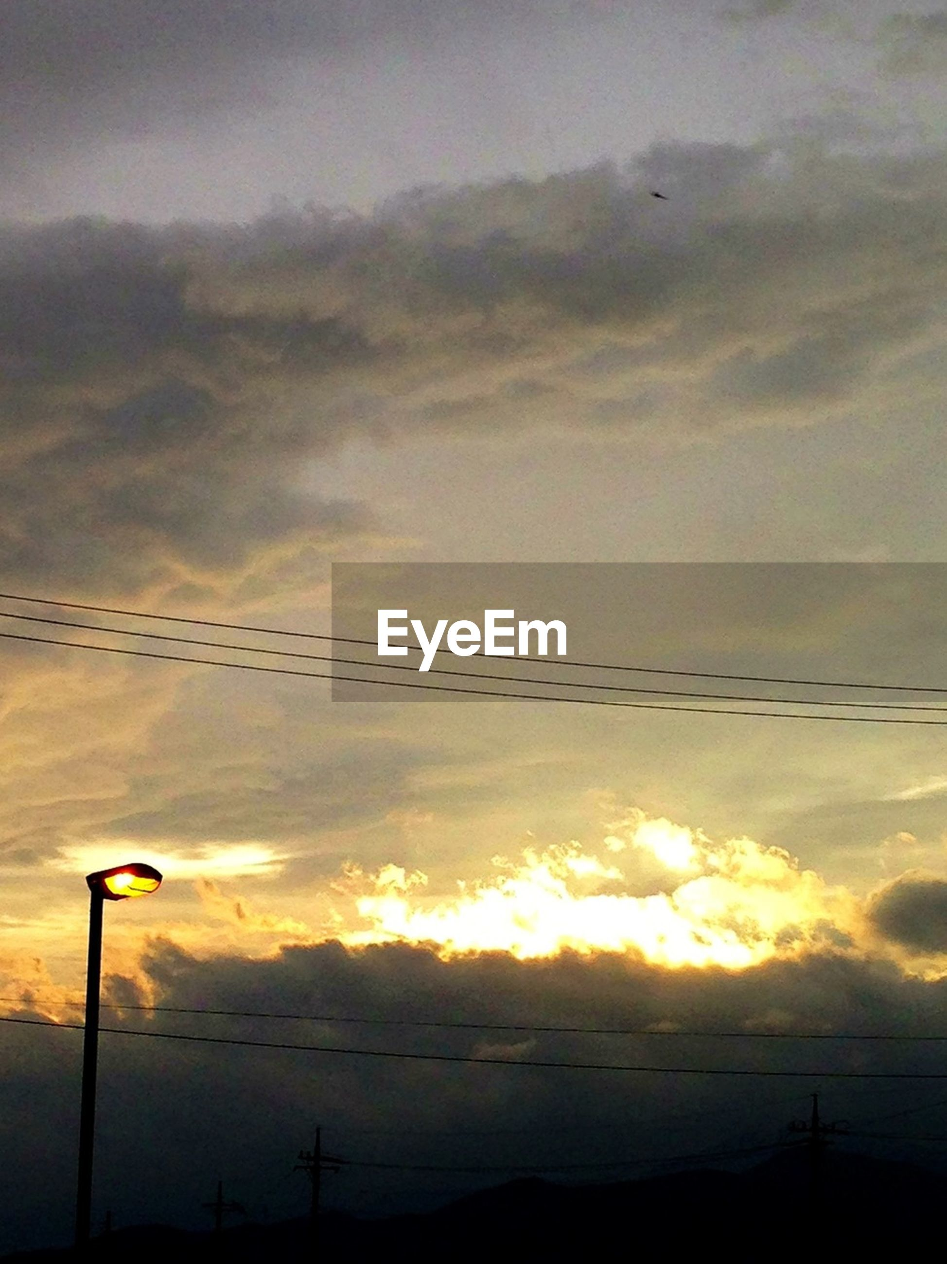 sunset, sky, silhouette, cloud - sky, low angle view, scenics, street light, beauty in nature, tranquility, tranquil scene, power line, cloudy, nature, orange color, dramatic sky, cloud, idyllic, lighting equipment, weather, electricity