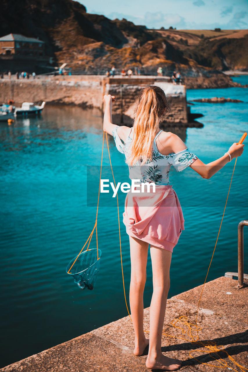 Rear View Of Woman Fishing On Pier In Sea