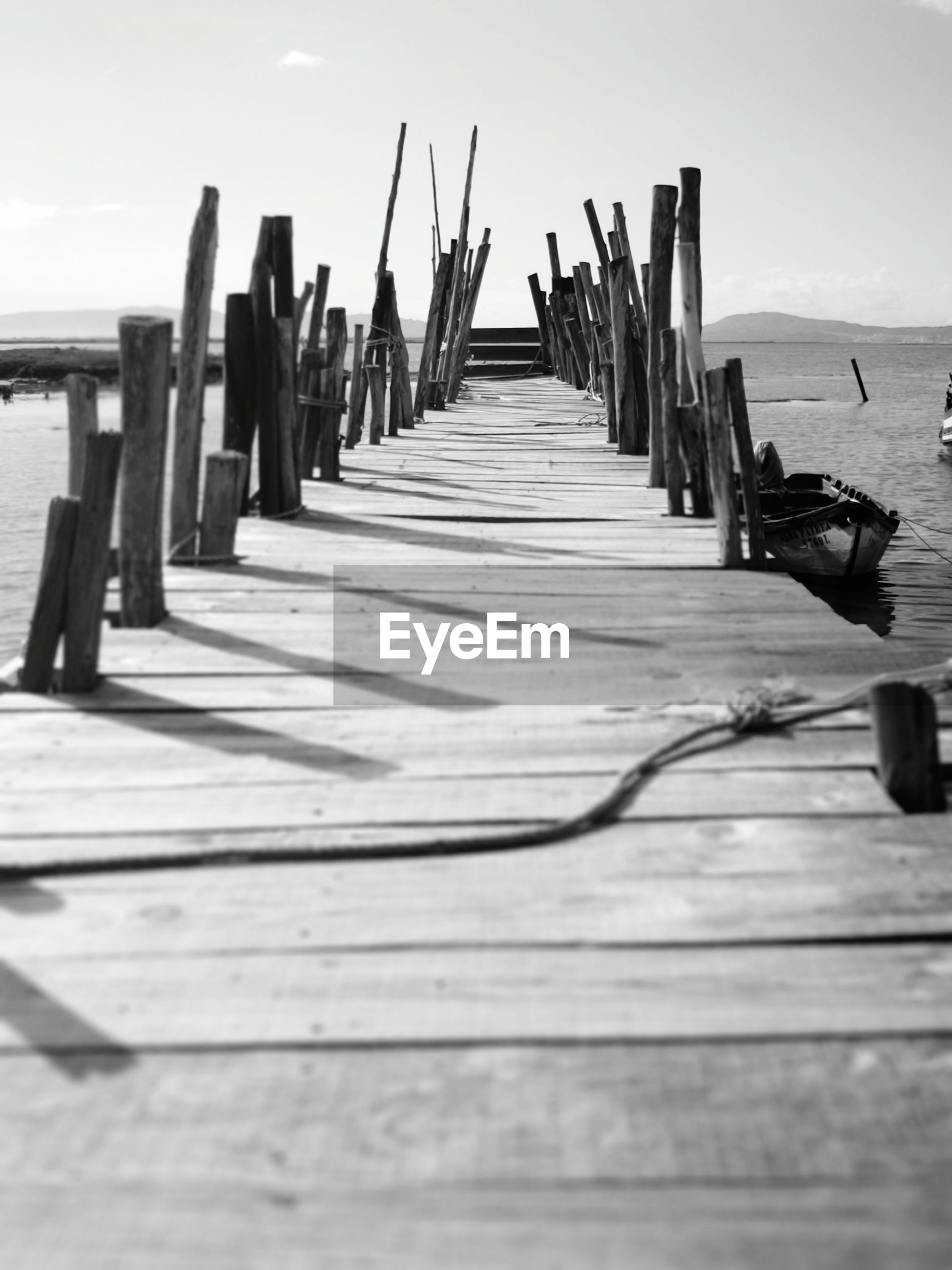 Wooden posts on pier at beach against sky