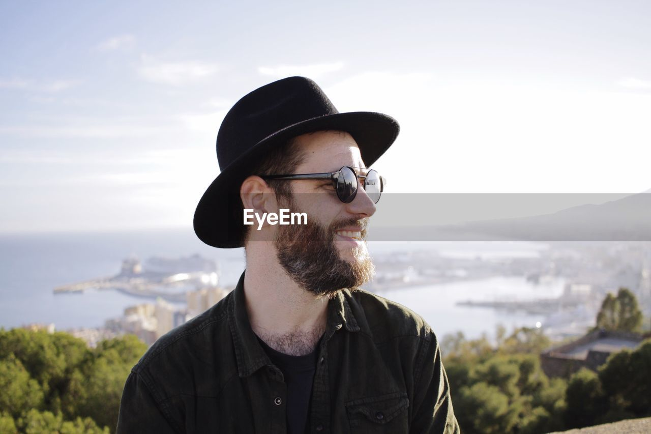 Close-Up Of Man Looking Away From Camera With Bay In The Background