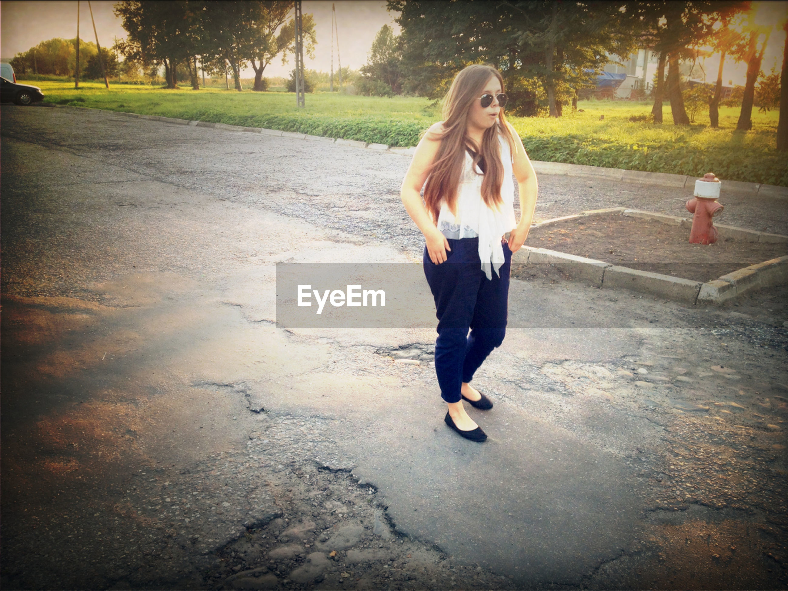 full length, casual clothing, lifestyles, person, leisure activity, young adult, front view, standing, street, walking, sunlight, portrait, tree, road, young women, looking at camera, shadow, outdoors