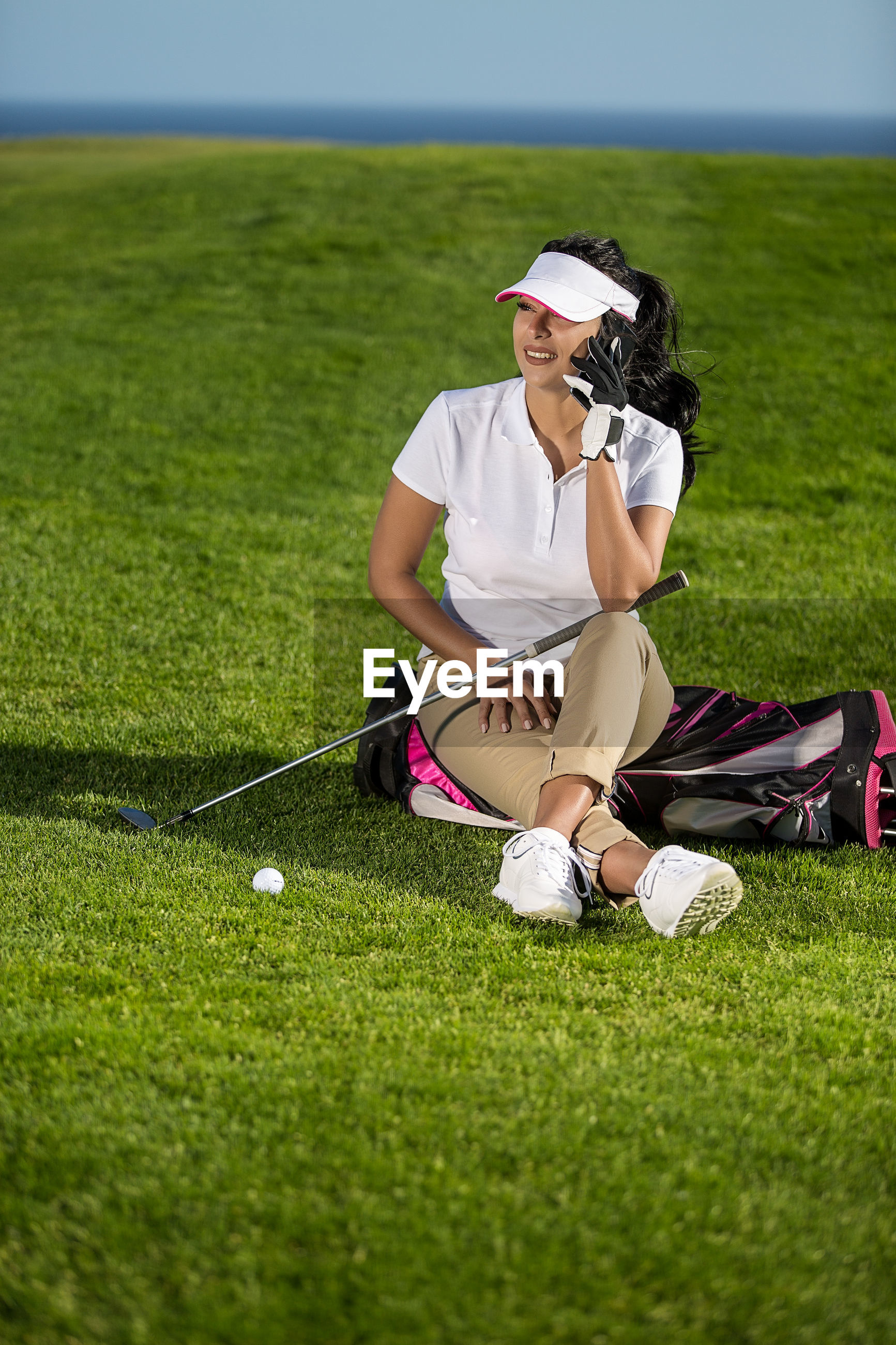Woman sitting on golf course during sunny day