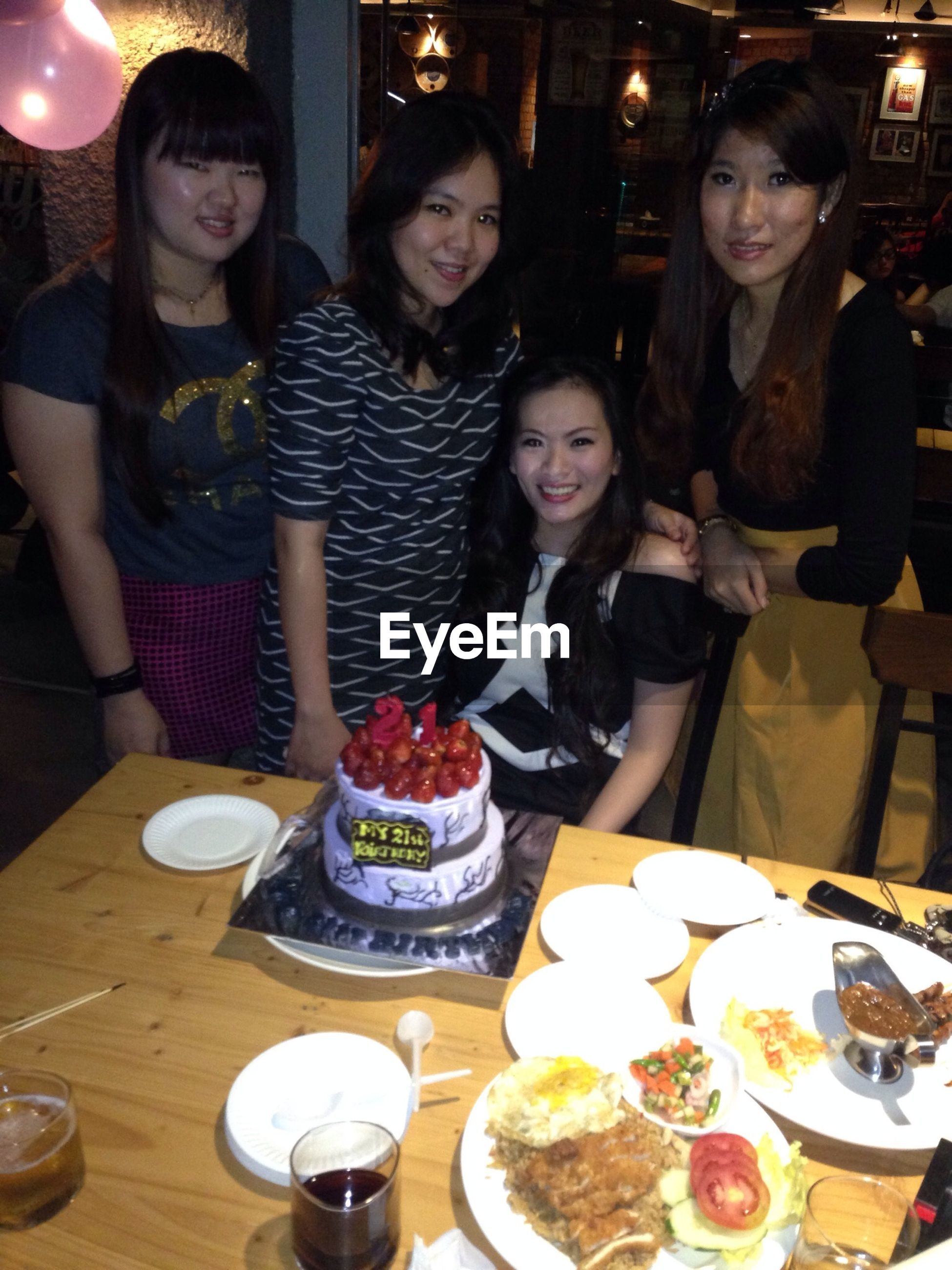 indoors, lifestyles, young adult, leisure activity, person, table, young women, togetherness, portrait, food and drink, looking at camera, happiness, front view, restaurant, casual clothing, smiling, sitting, friendship