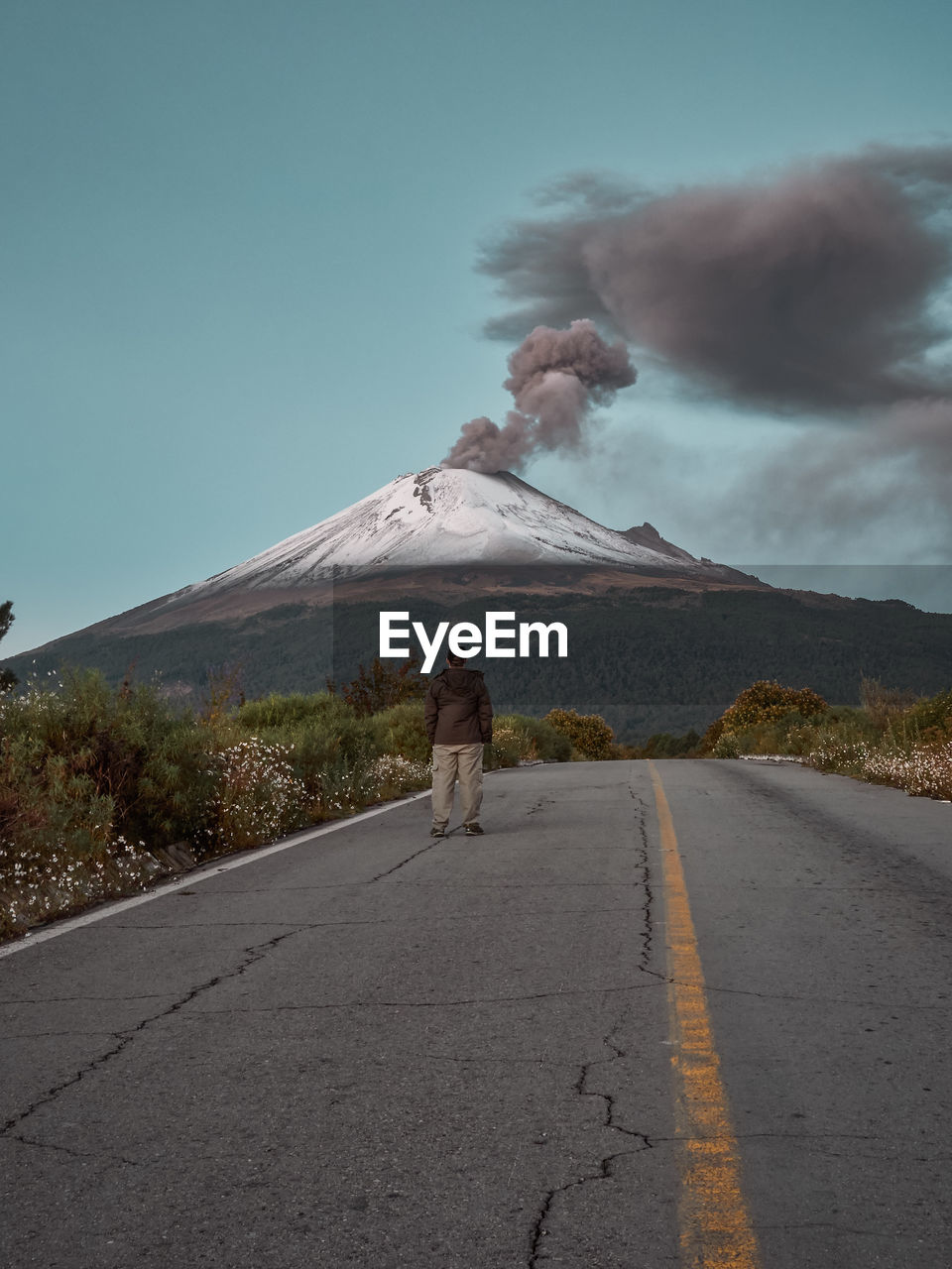Rear view of man on road against smoke emitting from volcano and sky