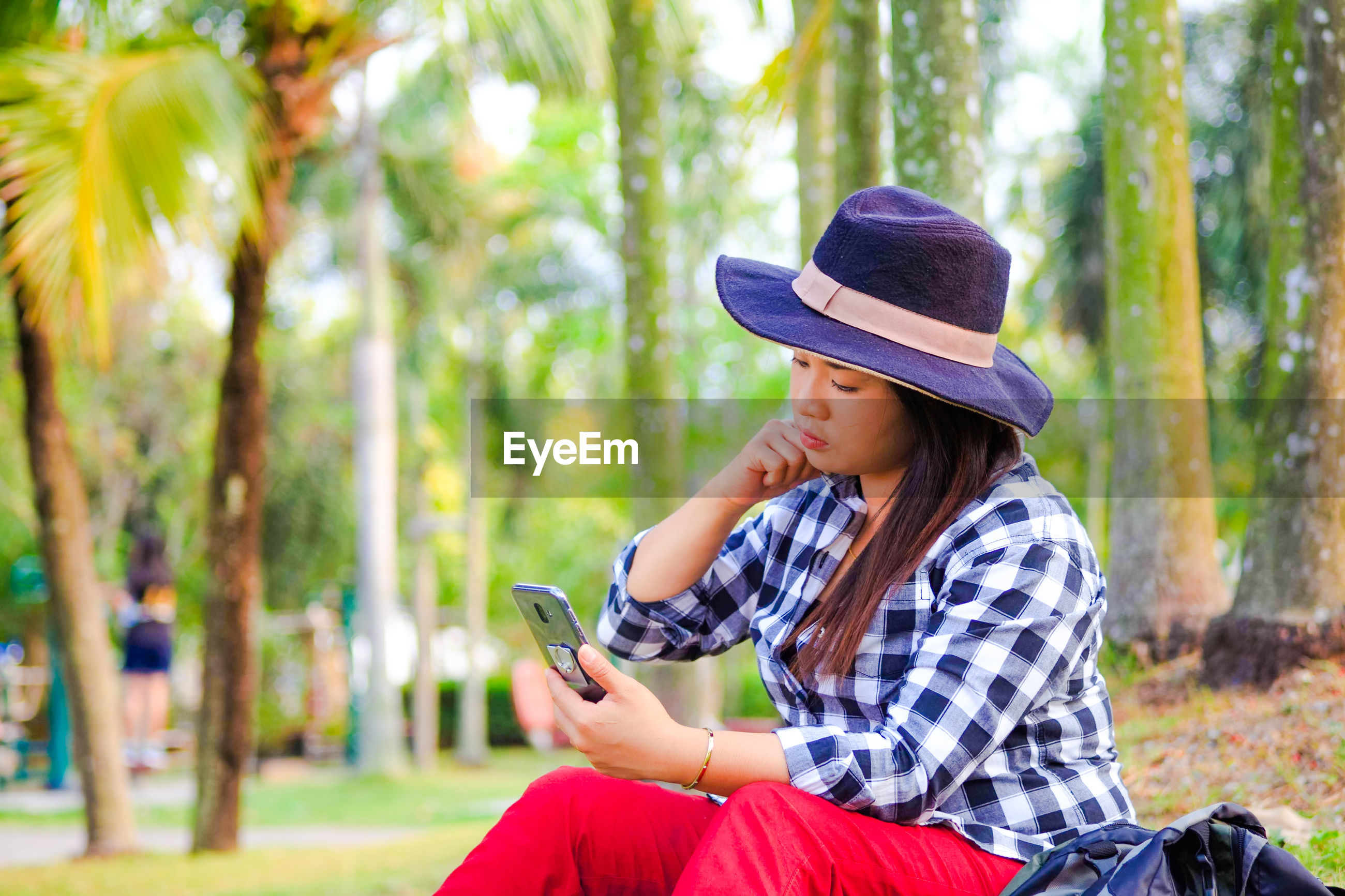 Woman using mobile phone while sitting against trees