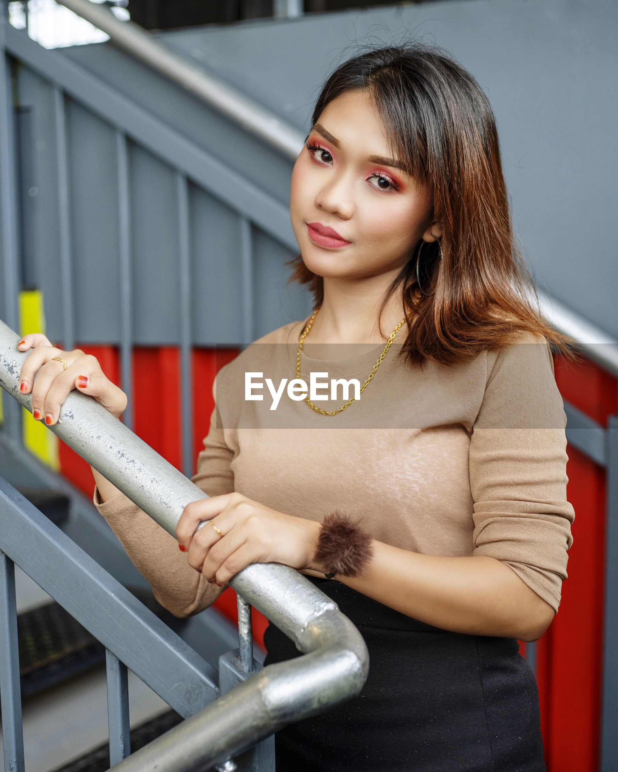 PORTRAIT OF SMILING YOUNG WOMAN STANDING BY RAILING