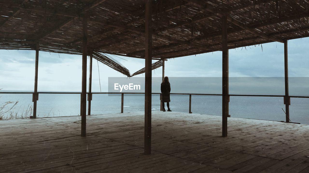 Rear view of woman standing in gazebo by sea