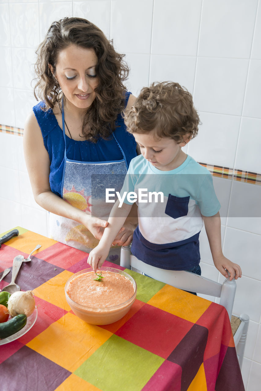 HIGH ANGLE VIEW OF MOTHER AND SON IN KITCHEN
