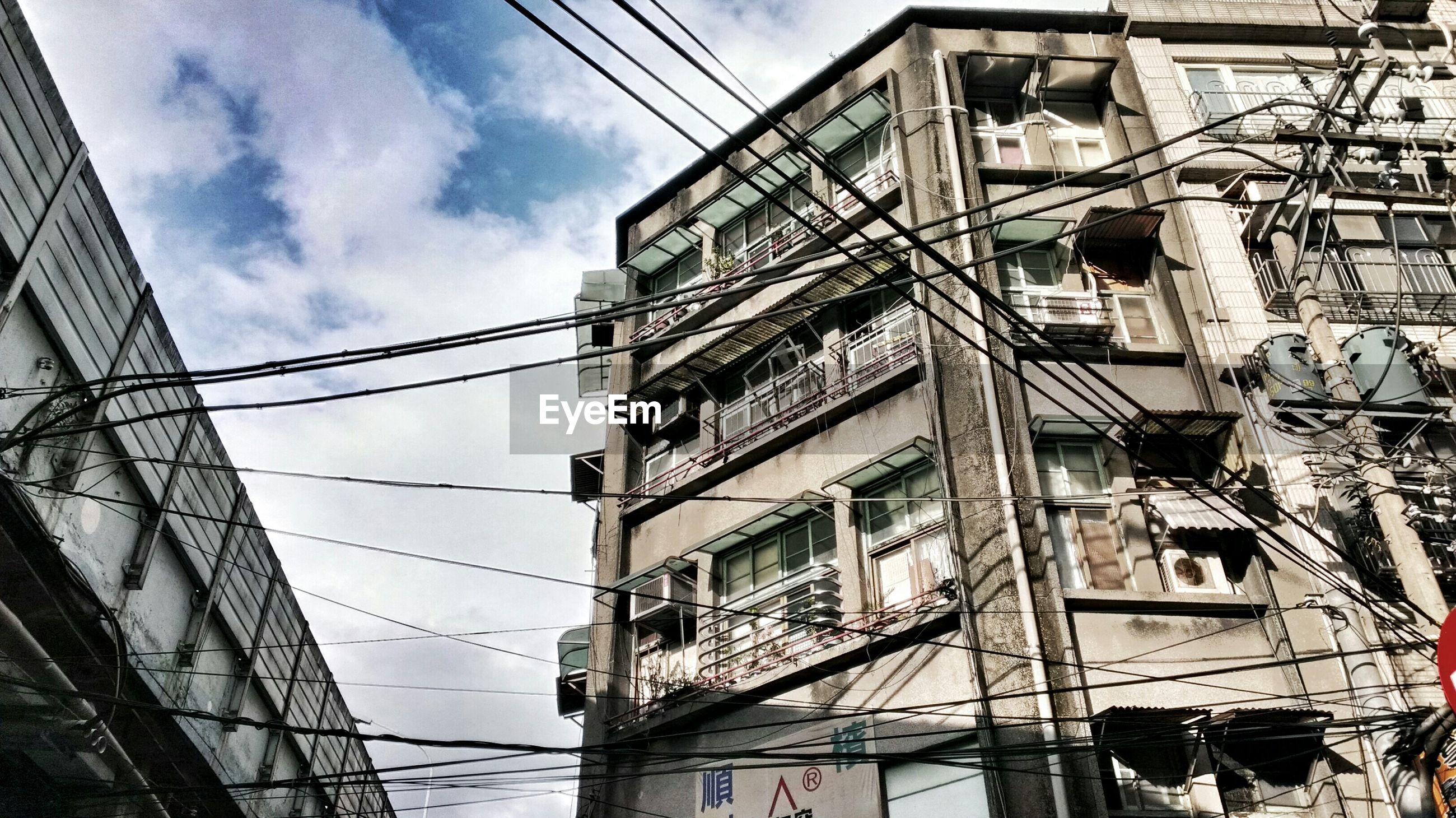 Low angle view of power cables against city building