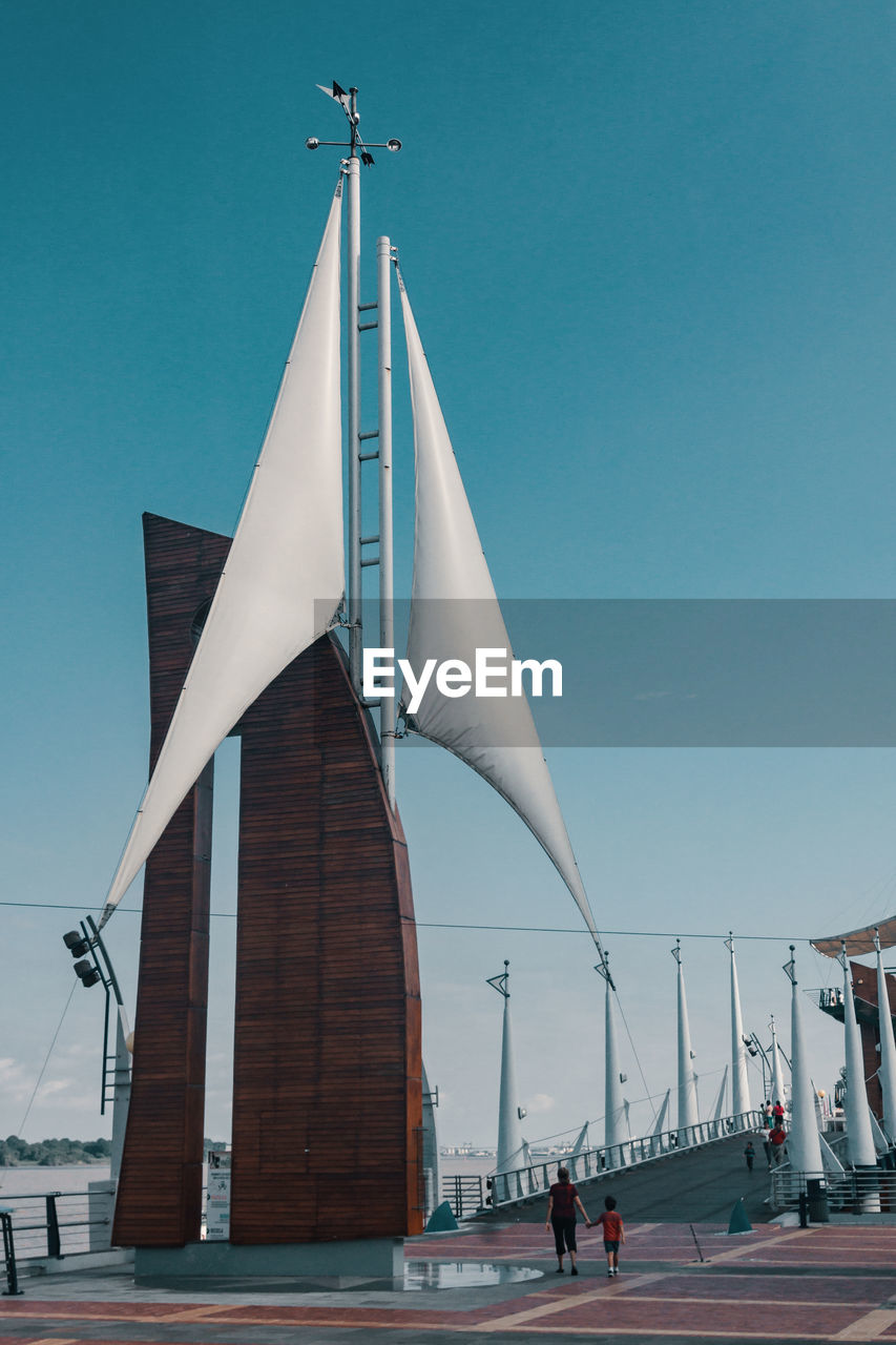 sky, architecture, built structure, building exterior, nature, real people, clear sky, day, incidental people, low angle view, blue, group of people, men, lifestyles, city, outdoors, street, walking, people, travel
