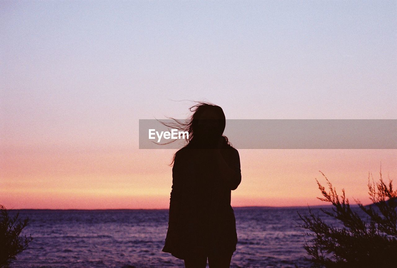 sky, sunset, sea, beauty in nature, one person, real people, beach, silhouette, scenics - nature, water, lifestyles, land, standing, leisure activity, orange color, nature, tranquility, women, horizon over water, outdoors, hairstyle, hair toss