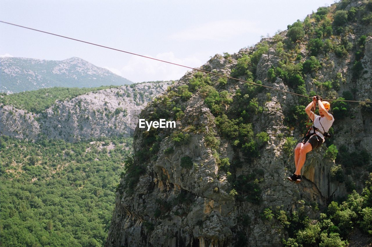Side view of man rappelling against lush foliage