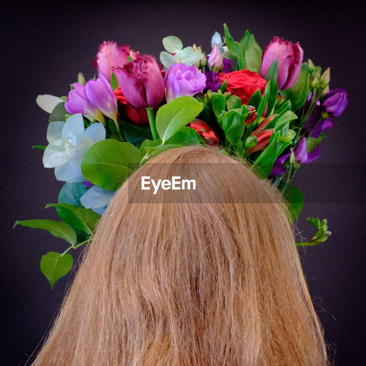 Rear View Of Woman With Flowers On Head Against Black Background