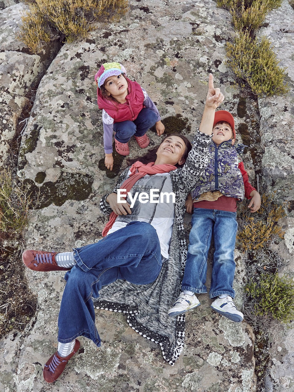 High Angle View Of Mother And Children On Rock