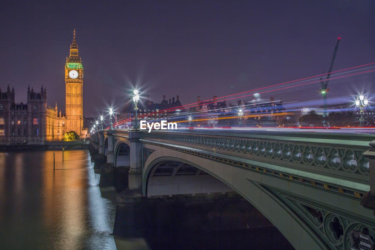 Westminster bridge over thames river against sky at night
