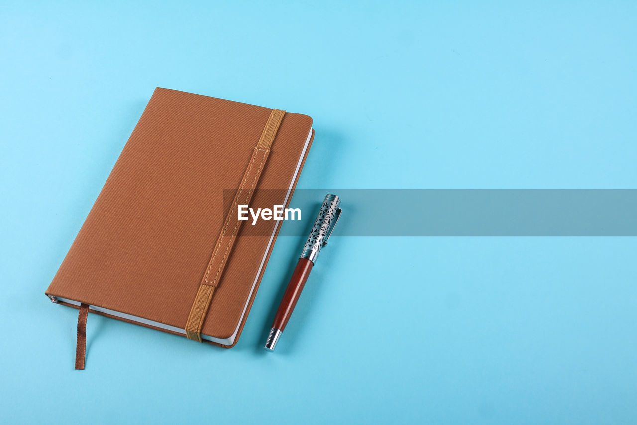 Close-Up Of Diary And Pen On Blue Background