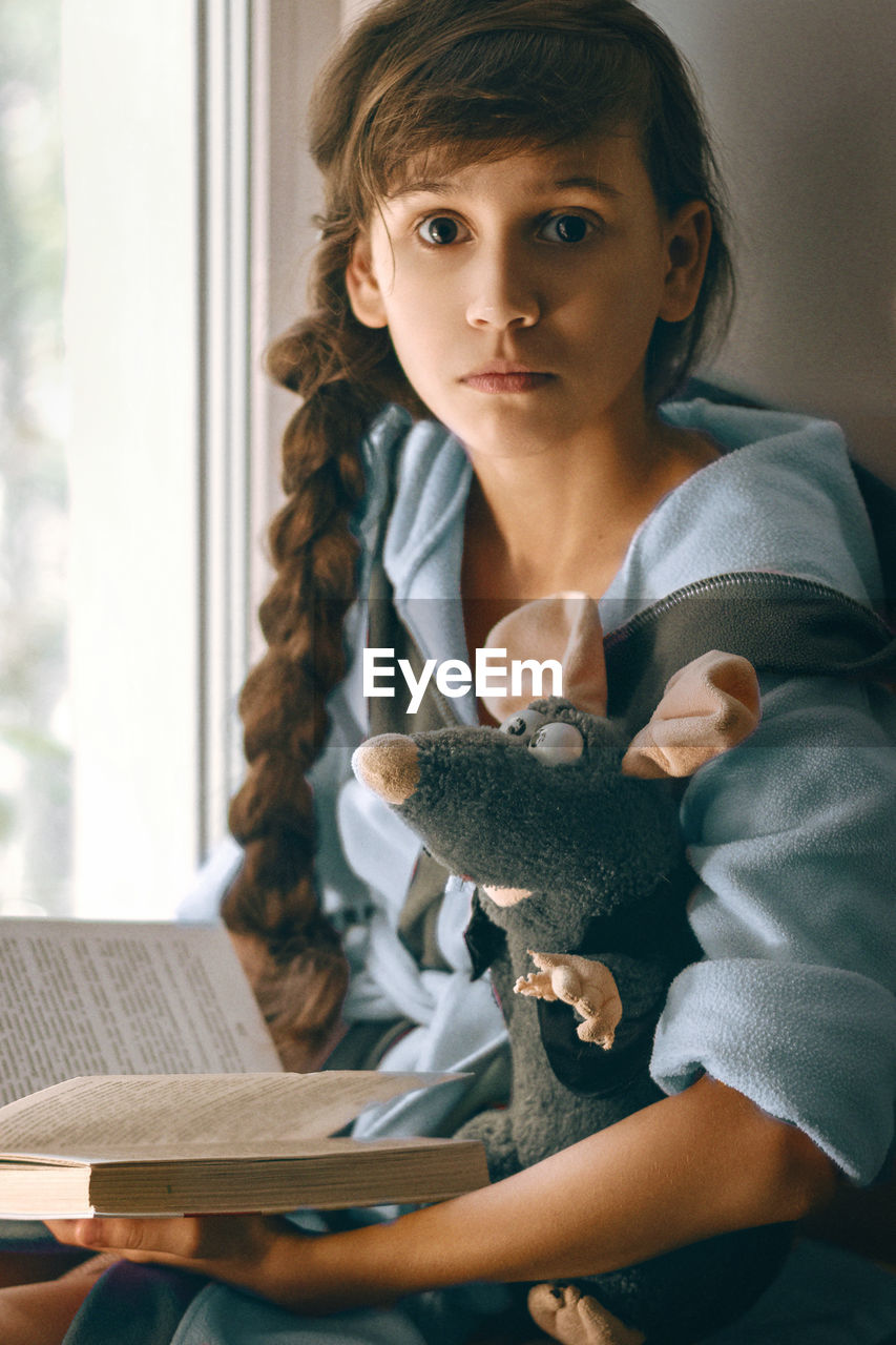 Portrait Of Girl With Stuffed Toy Holding Book At Home