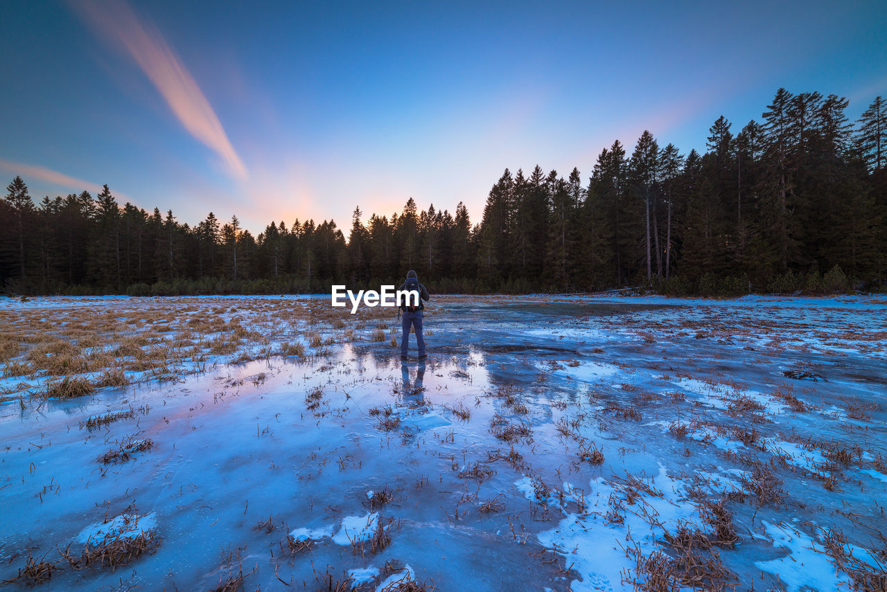 Man Standing On Frozen Lake Against Sky During Winter