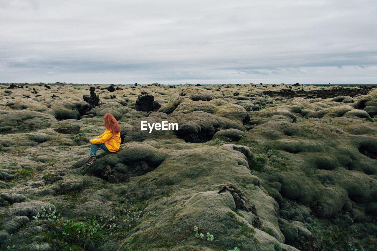 Woman sitting on rocky landscape against sky