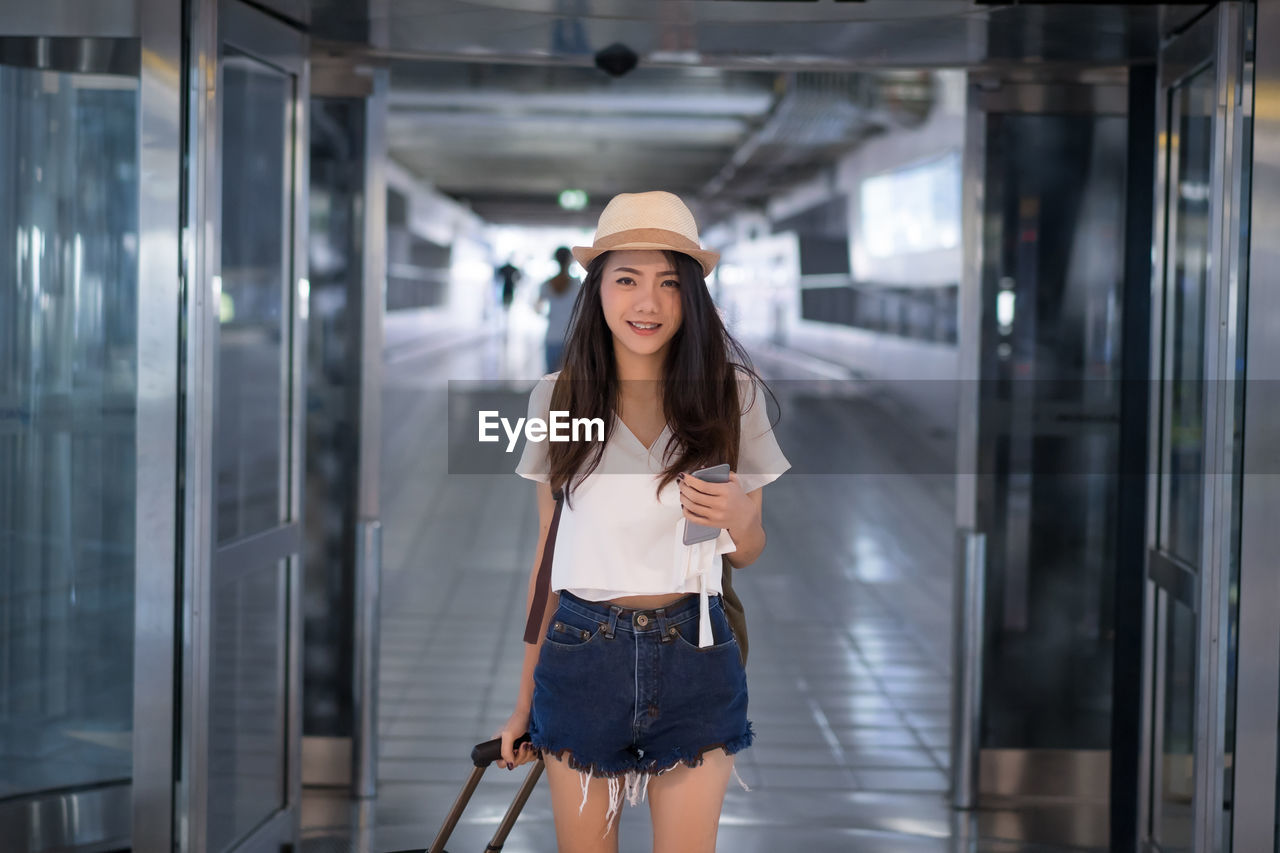 Portrait of smiling young woman standing in airport