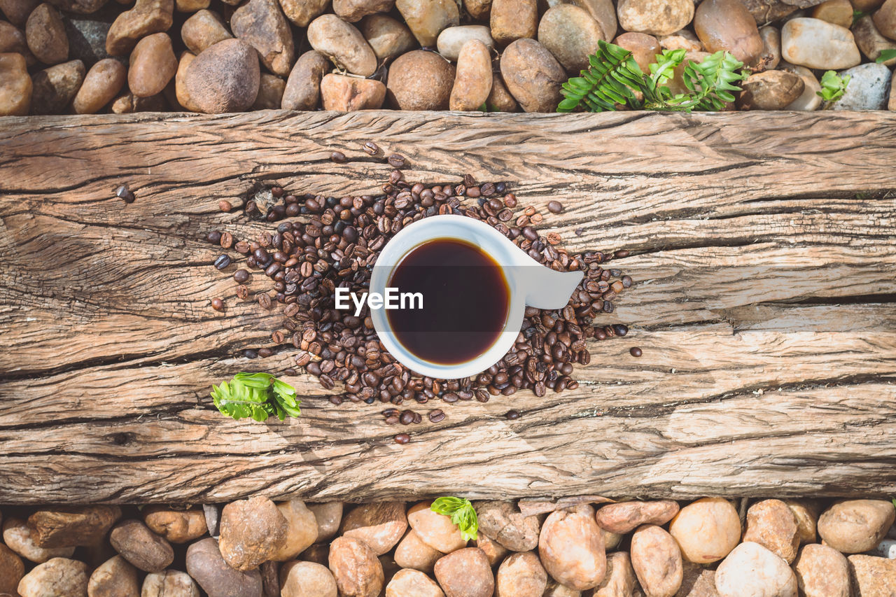Directly Above Shot Of Coffee Cup On Roasted Beans