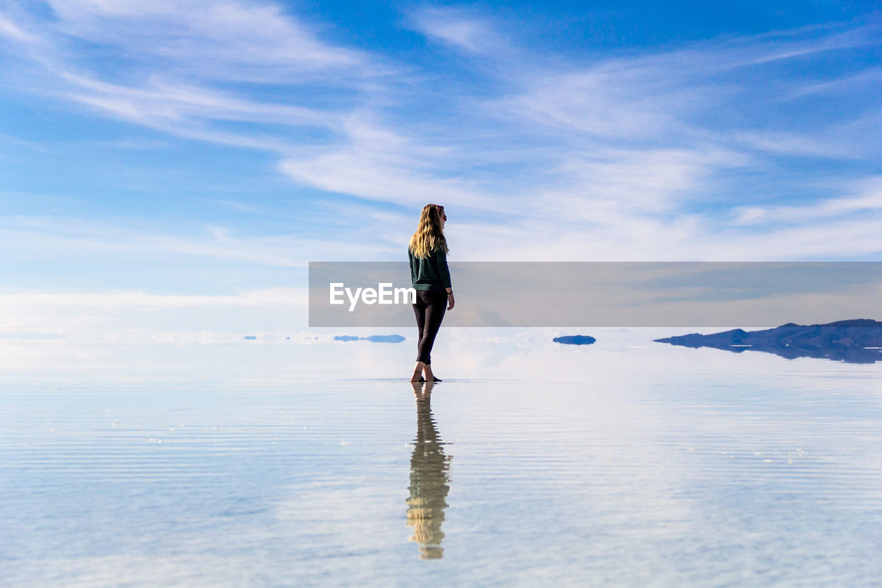 Rear View Of Young Woman Standing By Infinity Pool Against Cloudy Sky