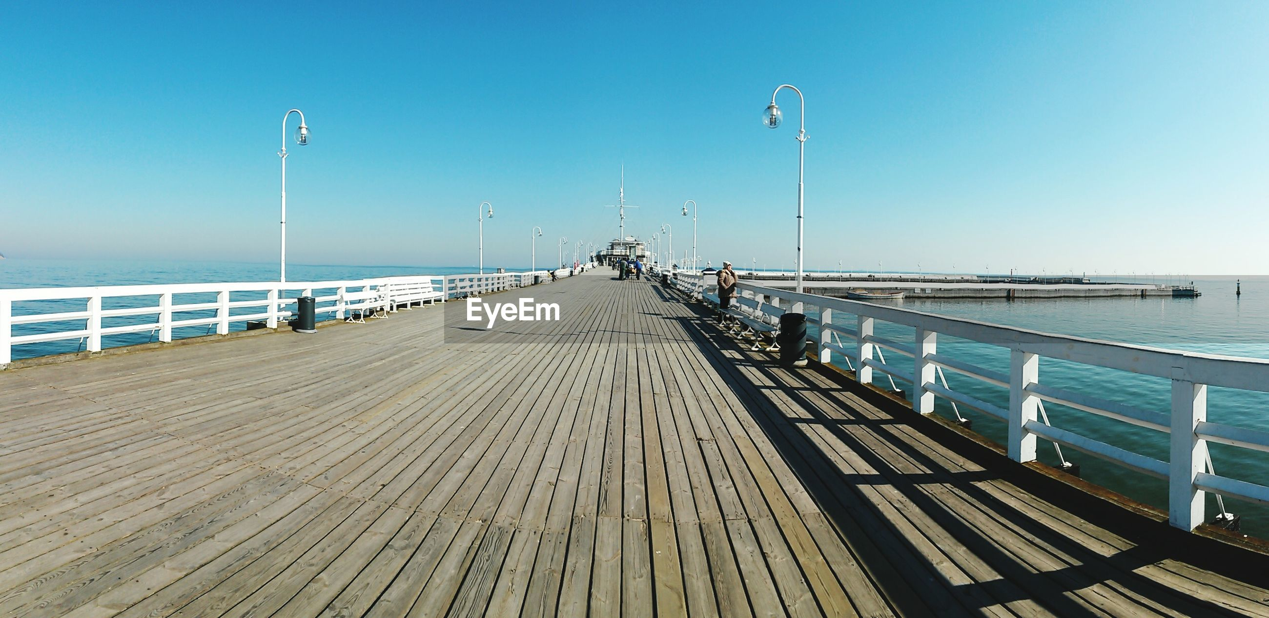 street light, clear sky, water, sea, pier, railing, the way forward, incidental people, horizon over water, long, blue, calm, lamp post, day, diminishing perspective, tranquil scene, ocean, tranquility, wood paneling