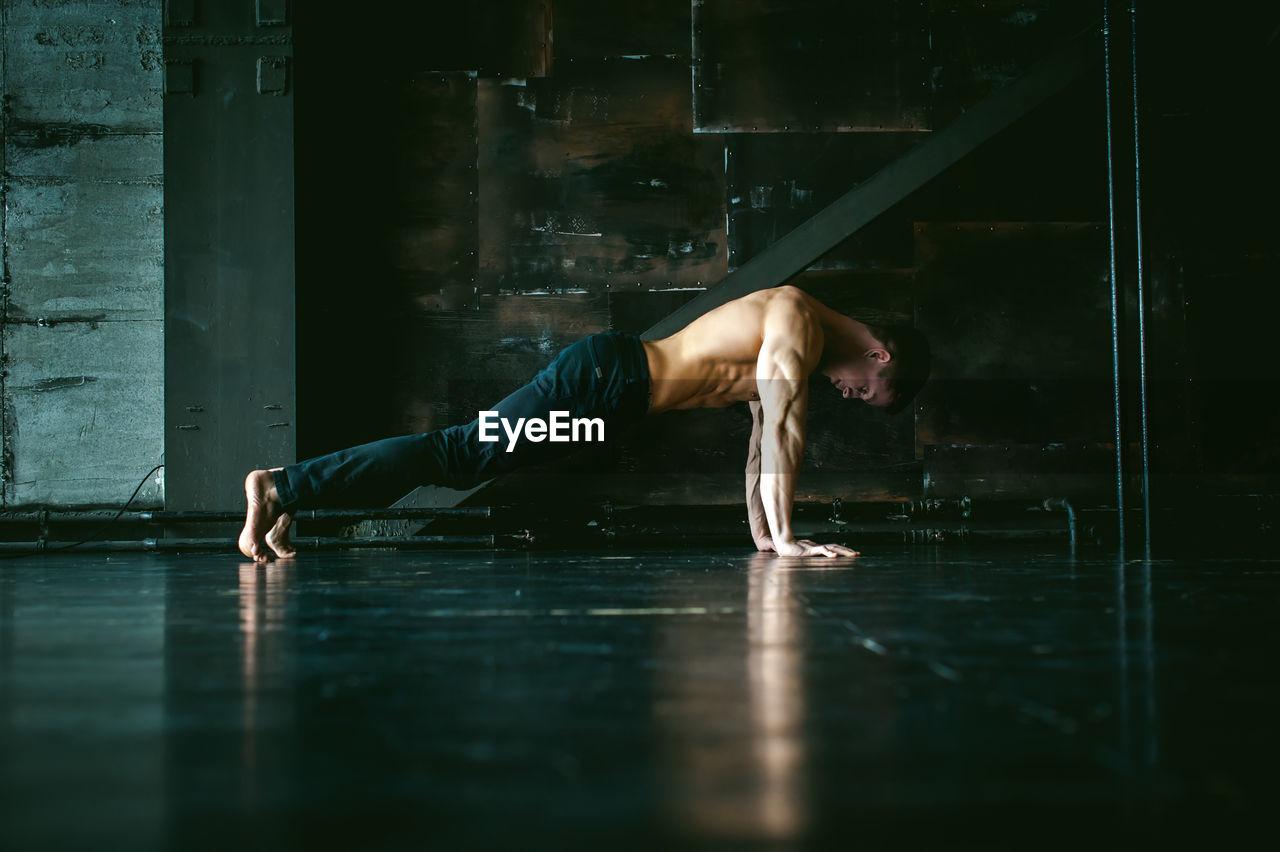 Full length of shirtless man exercising on floor