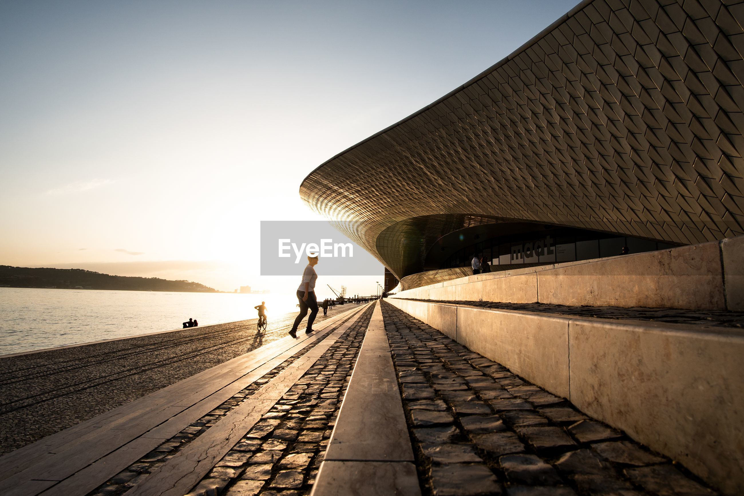 PEOPLE WALKING ON FOOTPATH DURING SUNSET