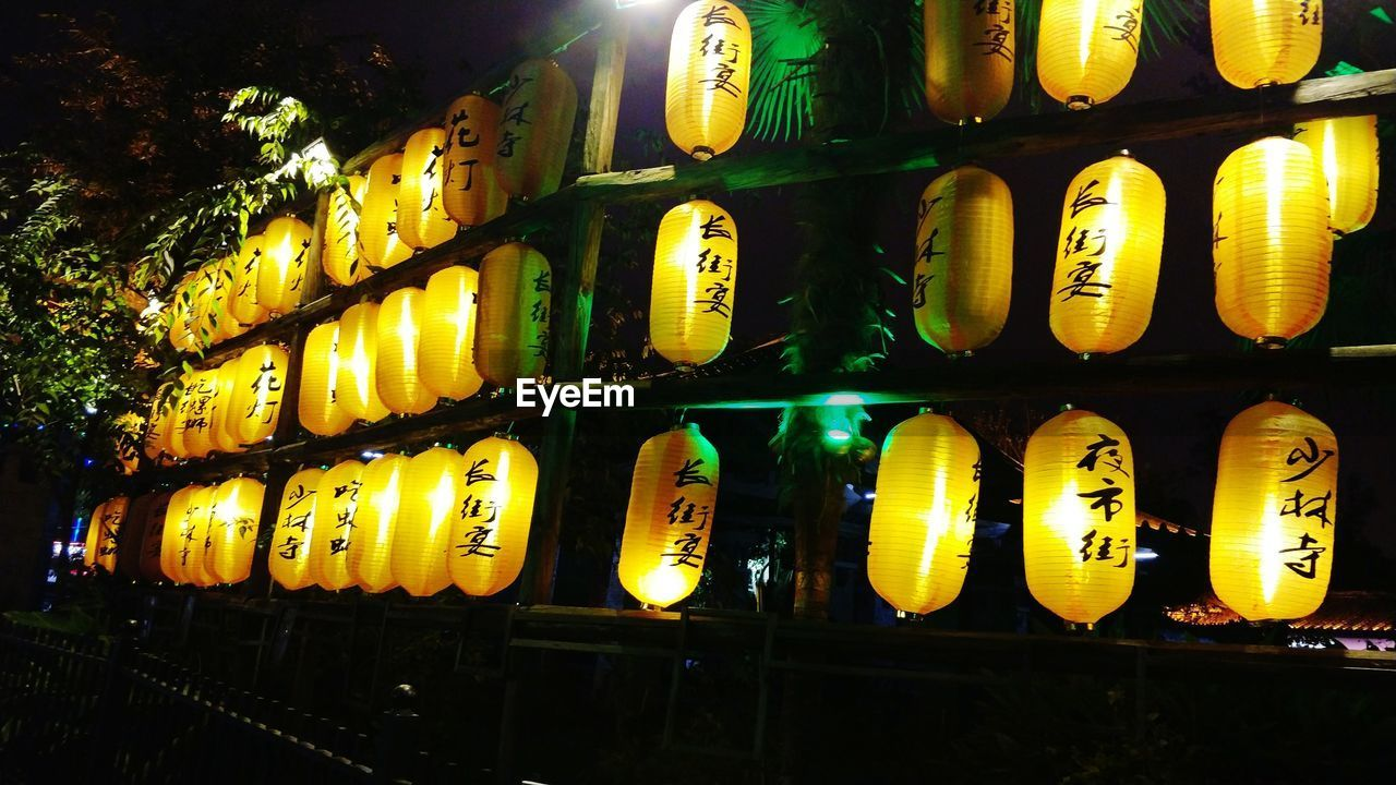 illuminated, in a row, night, yellow, no people, religion, lantern, place of worship, indoors, close-up