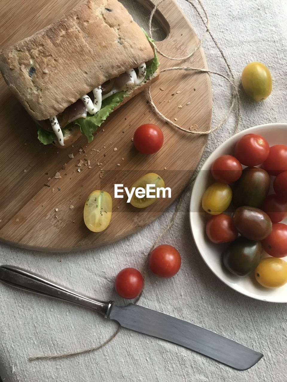 food, food and drink, healthy eating, fruit, tomato, freshness, table, still life, indoors, vegetable, wellbeing, high angle view, bread, knife, wood - material, eating utensil, olive, no people, cutting board, cherry tomato, table knife