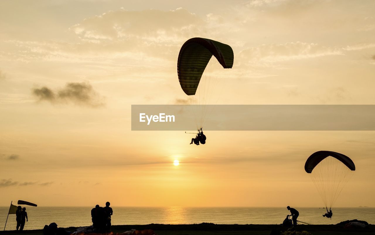 sky, extreme sports, sunset, adventure, sport, leisure activity, parachute, water, sea, silhouette, lifestyles, cloud - sky, paragliding, unrecognizable person, real people, beauty in nature, scenics - nature, group of people, nature, horizon over water, freedom, outdoors, parasailing