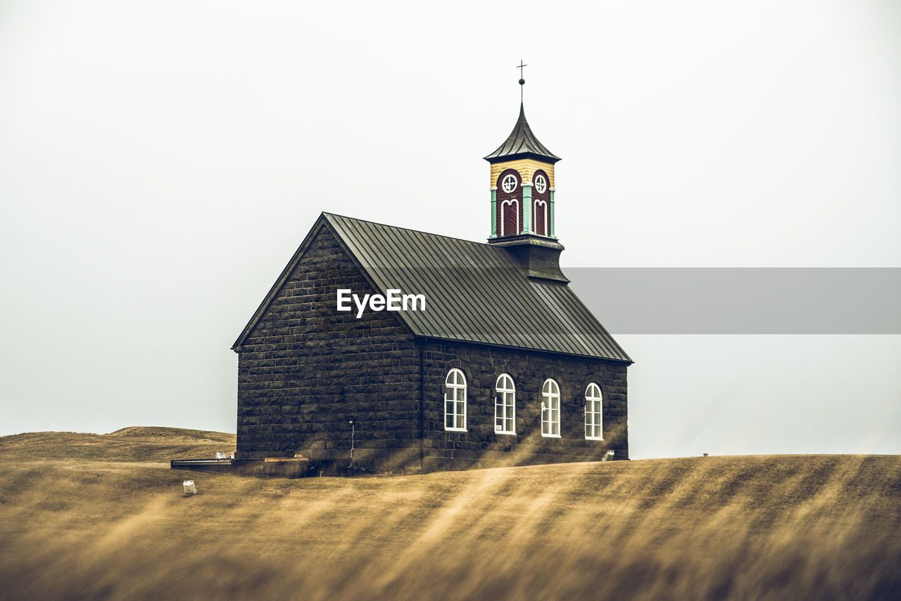 Exterior of wooden black church against clear sky
