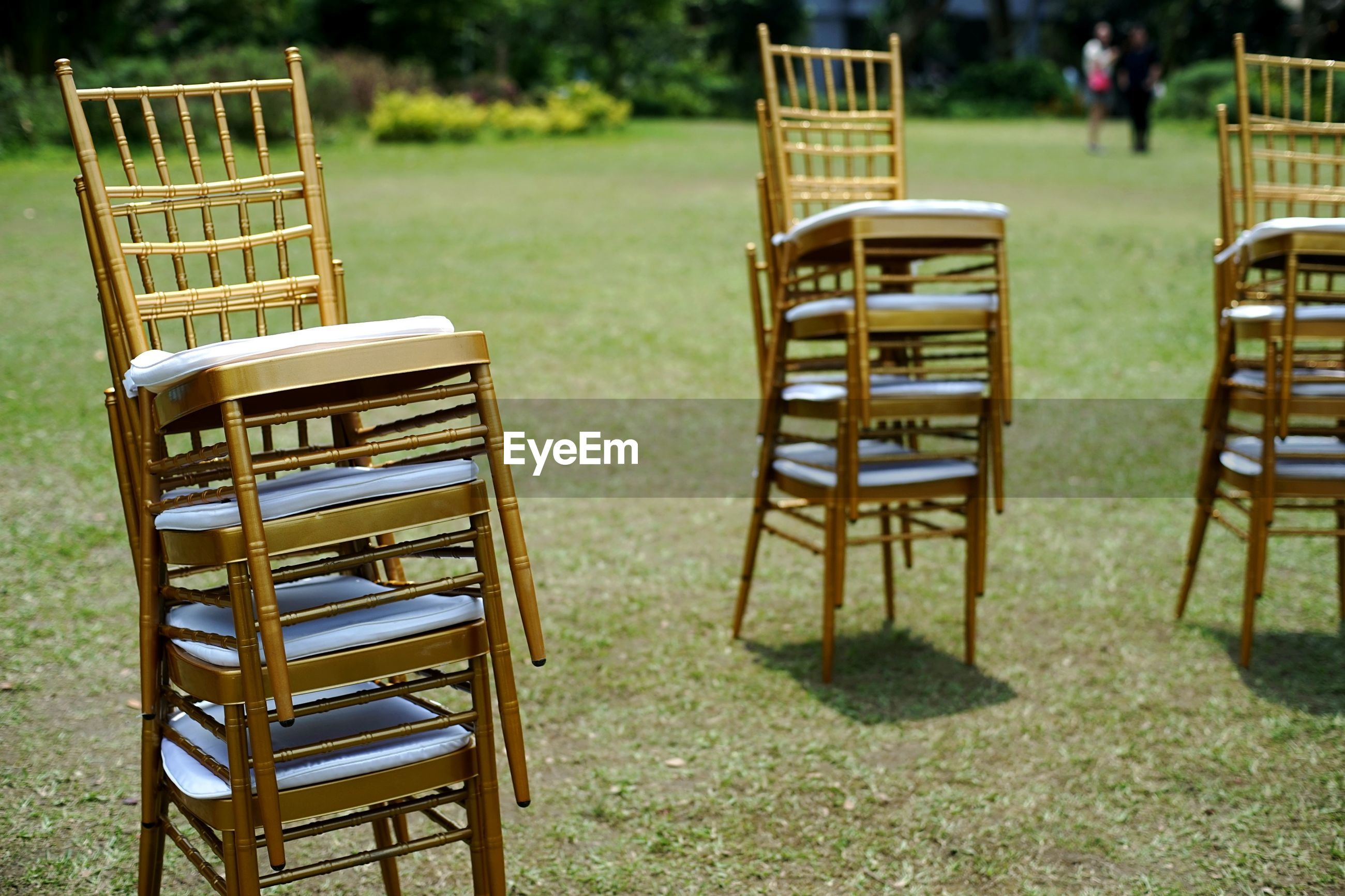 Stacked golden chairs in lawn