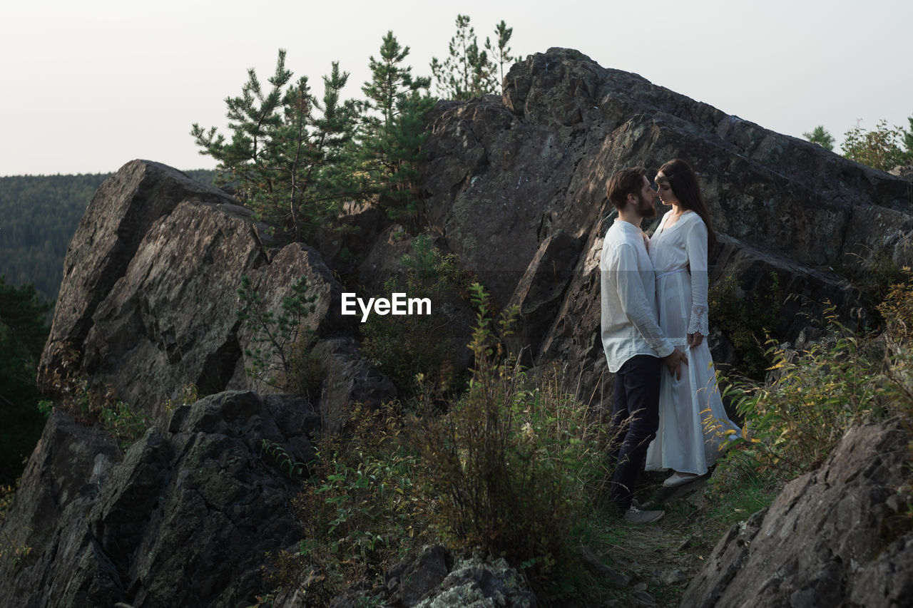two people, rock, rock - object, solid, leisure activity, plant, real people, women, standing, lifestyles, nature, full length, sky, young adult, people, casual clothing, togetherness, mountain, adult, tree, outdoors, couple - relationship, positive emotion, hairstyle