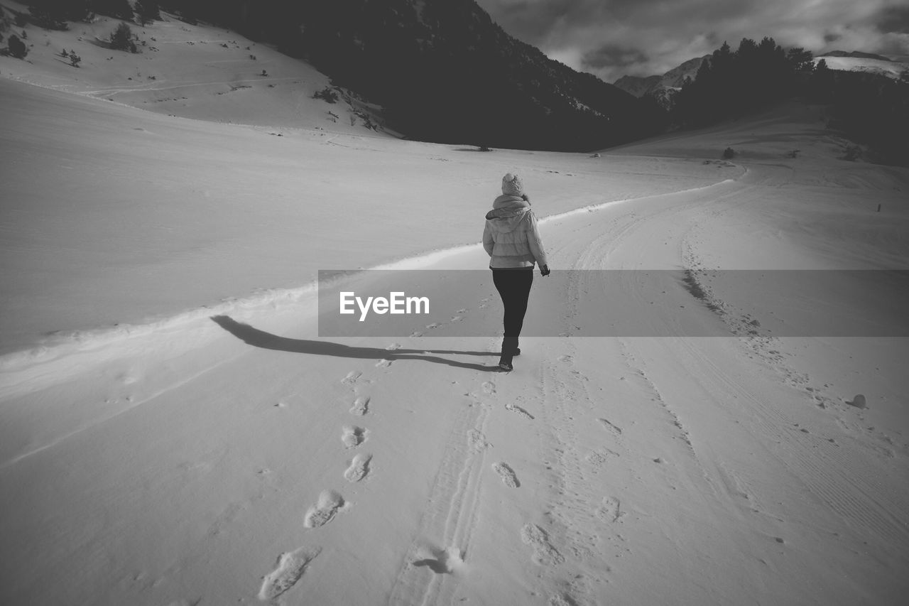 Rear view of person walking with footprints on snow covered landscape